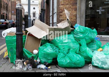 Müll in Säcken an einer Straßenecke entlang Hanbury street London uk Stockfoto