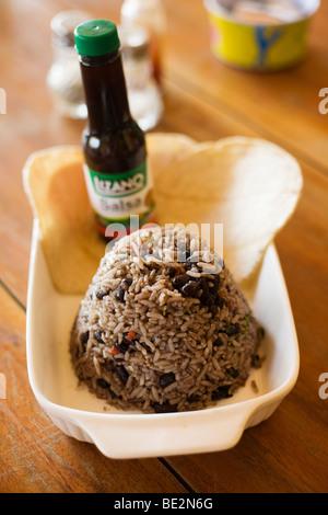 Lizano Sauce gegossen wird, auf einen Teller mit Gallo Pinto, eine typische und traditionelle Gericht in Costa Rica - Stockfoto