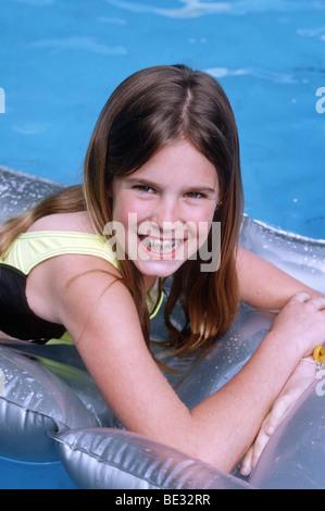 Kaukasische weibliche Preteen schwimmend auf einem Floß in einem Schwimmbad - Stockfoto