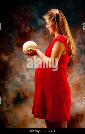 Schwangere Frau mit Strauß Ei blickte auf ei - Stockfoto
