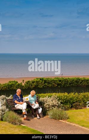 Zwei Rentner sitzen auf einer Strandpromenade Bank lesen Sie ihre Zeitung am Hunstanton, North Norfolk, Großbritannien - Stockfoto