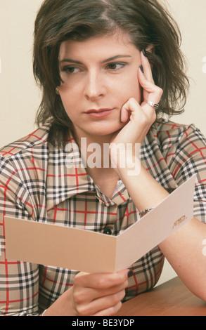 Traurige Frau halten Postkarte in der hand und sah von der Grußkarte, die ihre traurigen SerieCVS100024101 gemacht - Stockfoto