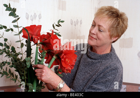 Ältere Frau arrangieren Blumen Ionen-vase - Stockfoto