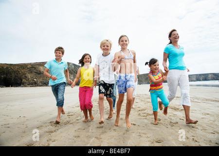 Frau, drei Mädchen und zwei jungen am Strand entlang spazieren hand in hand, lachen, Bretagne, Frankreich, Europa - Stockfoto