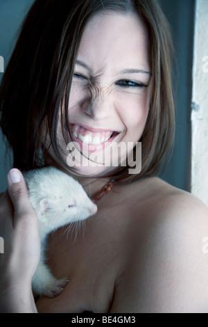 Junge Frau streicheln ein Frettchen, Porträt - Stockfoto