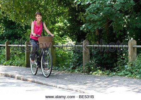 Eine junge Frau mit dem Fahrrad entlang einer Landstraße - Stockfoto