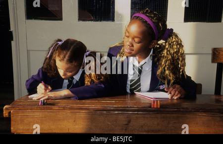 Zwei kleine Mädchen in einem Klassenzimmer.  Ein Mädchen nimmt einem heimlichen Blick ihrer Freundin Arbeit. - Stockfoto