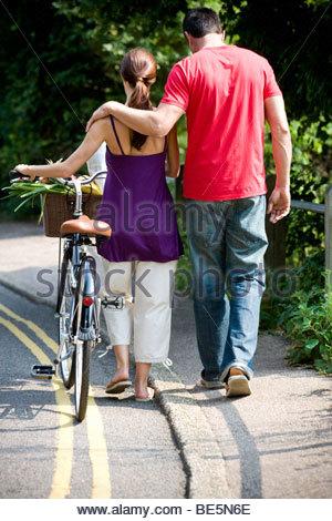 Ein Mann und eine Frau zu Fuß mit dem Fahrrad und shopping - Stockfoto