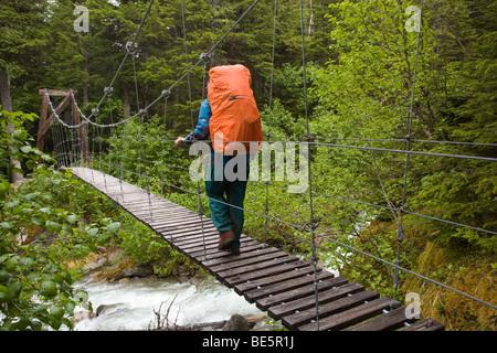 Weibliche Wanderer mit Rucksack Kreuzung Hängebrücke über taja Fluss, in der Nähe der historischen Canyon City, - Stockfoto