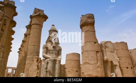 Luxor Tempel Komplex, Statue von Ramses II. im ersten Hof zwischen zwei massiven Säulen, Luxor-Tempel, Ägypten, - Stockfoto