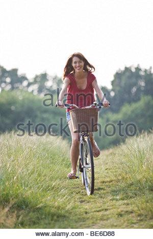 Eine junge Frau mit dem Fahrrad durch ein Feld - Stockfoto