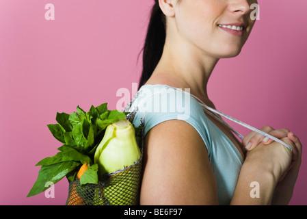 Frau Sack von frischem Gemüse über Schulter getragen - Stockfoto