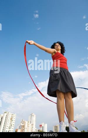Junge Frau mit Band im Wind, lächelnd, niedrigen Winkel Ansicht - Stockfoto