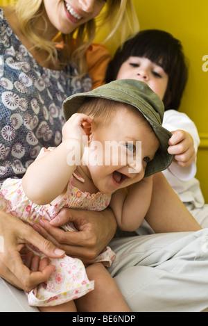 Baby Mädchen sitzen mit Mutter und Bruder, Hut und lachen - Stockfoto