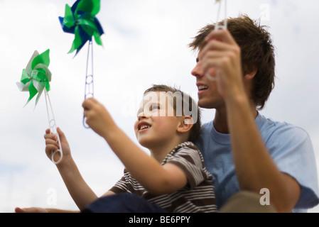 Vater und seinem kleinen Sohn halten Windräder - Stockfoto