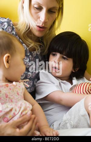 Mutter mit Tochter und Sohn auf Schoß, Nahaufnahme - Stockfoto
