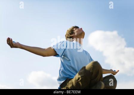 Junger Mann im Freien zu meditieren, hält Yin Yang Kugeln - Stockfoto