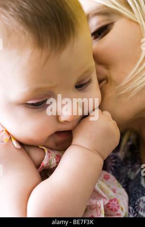Mutter küssen kindlichen Wange, close-up - Stockfoto