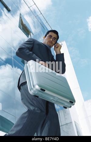 Geschäftsmann mit Aktenkoffer mit Handy vor Bürogebäude - Stockfoto