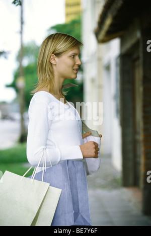 Frau, die Einkaufstaschen auf Arm Fenster shopping, seitliche Ansicht - Stockfoto