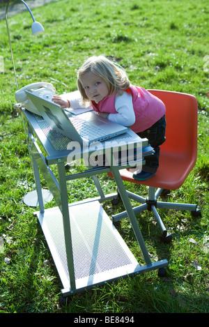 Kleines Mädchen stand auf Bürostuhl Schreibtisch im Feld, mit Laptop-Computer zu spielen, Blick in die Kamera - Stockfoto