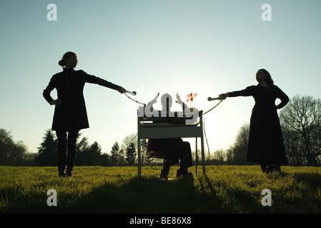 Frau sitzt am Schreibtisch im Feld mit Handzeichen, Weibchen halten, Festnetz-Telefone auf beiden Seiten, Silhouette - Stockfoto