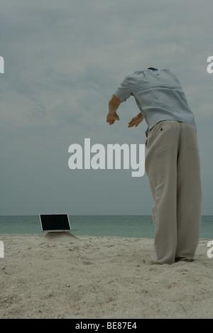 Mann am Strand stehen, bücken auf Laptop-Computer, Rückansicht - Stockfoto