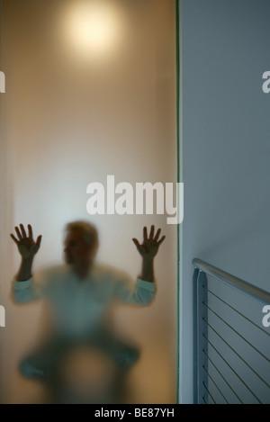Mann hocken hinter Fenster, Hände drückte gegen Glas - Stockfoto