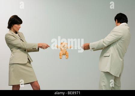 Professionelle paar spielen Tauziehen mit Teddybär - Stockfoto