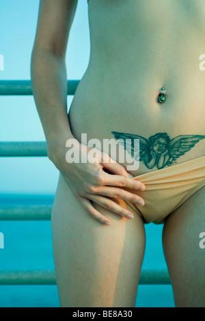 Frau, senken Bikiniunterteil enthüllen Tattoo von cherub - Stockfoto