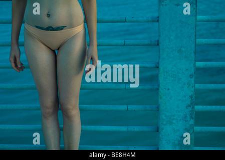 Junge Frau im Bikini allein durch Geländer am Meer Gehweg - Stockfoto
