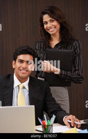 Geschäftsmann und Frau lächelt in die Kamera - Stockfoto