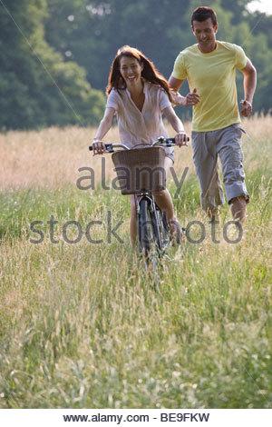 Eine junge Frau mit dem Fahrrad durch ein Feld mit ihrem Freund hinterher laufen - Stockfoto