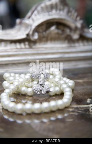 Funkelnde weiße Perle Armband auf dem Marmor Oberfläche aus einem Schminktisch. - Stockfoto