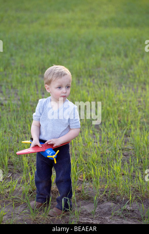 Ein Portrait eines jungen Mannes hält ein Spielzeugflugzeug im freien - Stockfoto