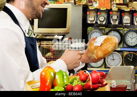 Den Preis für ein Brot mit einem Barcode-Lesegerät Scannen Verkaufssachbearbeiter - Stockfoto