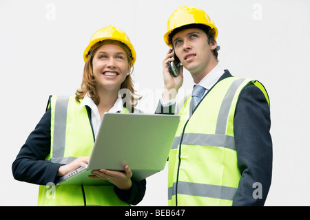 Team von young Professionals auf einer Baustelle Schutzhelm tragen und mit Laptop und Handy - Stockfoto