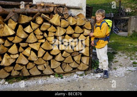 Kleiner Junge 8, beim Wandern, stehen neben einem Holzstapel - Stockfoto