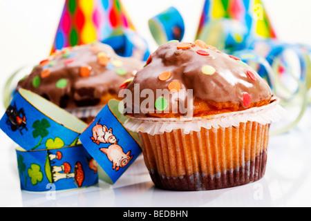 Muffins und Luftschlangen, symbolisches Bild für Karneval oder den Kindergeburtstag - Stockfoto