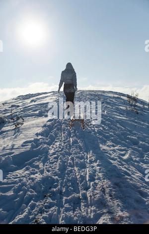Junge Frau ziehen Schlitten im Schnee - Stockfoto