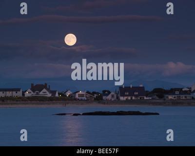 Trearddur, Anglesey, North Wales, UK. MONDAUFGANG über TREARDDUR BAY mit dem Vollmond reflektiert das Meer in der - Stockfoto