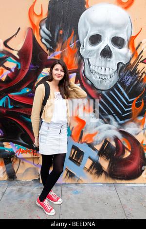 Porträt einer jungen Frau stehend mit bunten Graffiti auf den Straßen von San Francisco, USA - Stockfoto