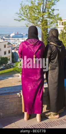 Zwei einheimische Frauen, die mit Blick auf Hafen von Tanger Marokko - Stockfoto