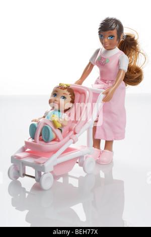 Mutter-Puppe mit Baby Mädchenpuppe in einem Miniatur-Kinderwagen-buggy - Stockfoto