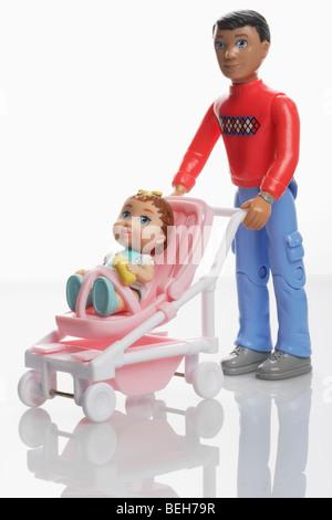 Vater-Puppe mit Baby Mädchenpuppe in einem Miniatur-Kinderwagen-buggy - Stockfoto