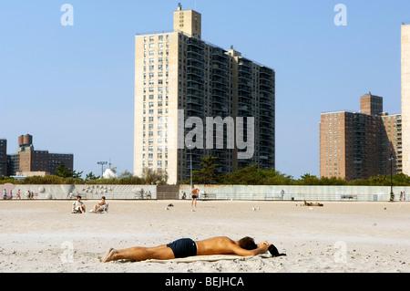 Ein Mann schläft auf den Sand am Strand von Coney Island, Brooklyn, New York. Hochhaus-Wohnprojekte sind im Hintergrund - Stockfoto