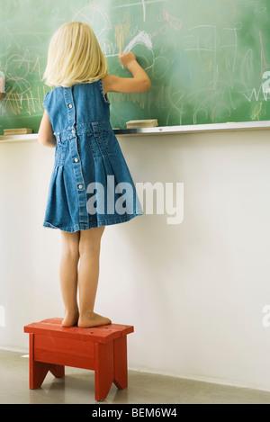 Kleines Mädchen auf Hocker stehend, Gekritzel auf Tafel, Rückansicht