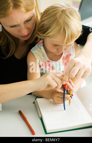 Frau helfen kleine Mädchen mit Kompass zeichnen - Stockfoto