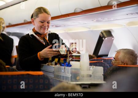 Flugbegleiter / Luft Stewardess serviert Getränke und Snacks für Passagiere von einem Wagen Karren während einem - Stockfoto