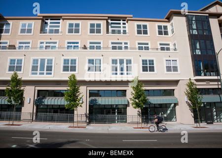 Radfahrer fährt vor Mischnutzung Wohnen. Wohn-Eigentumswohnungen und Büros, Verkaufsflächen. CA-USA - Stockfoto